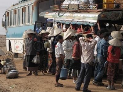 Handlarki oblegające autobus przy przeprawie przez Mekong