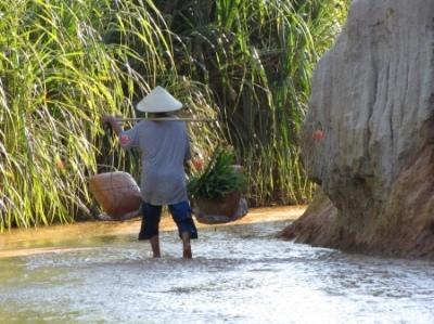 Wietnamczyk z nosidłami w strumyku