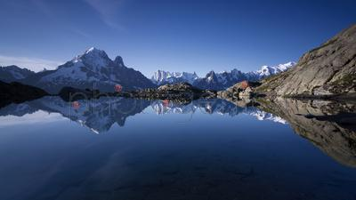Snowcapped mountains reflecting in tranquil Lac blanc lake, France