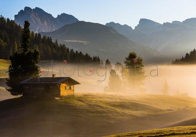 House covered in fog with mountains in background, Dolomites, Italy