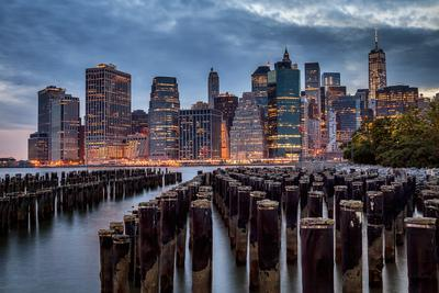 Lower Manhattan skyline at dusk with wooden groyne in foreground, New York City, New York State, USA