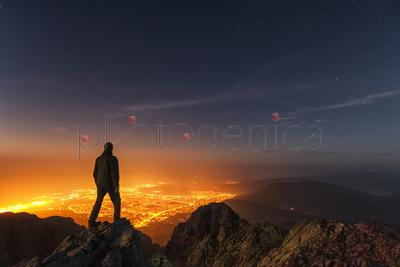 Man standing on mountain peak at night and looking down at illuminated city, Sinite Kamani Park, Balkan Mountains, Sliven, Bulgaria