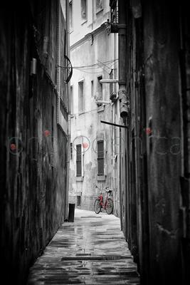 Red bicycle parked in narrow street