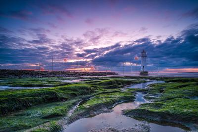 Lighthouse at beach at sunset, Merseyside, England, UK