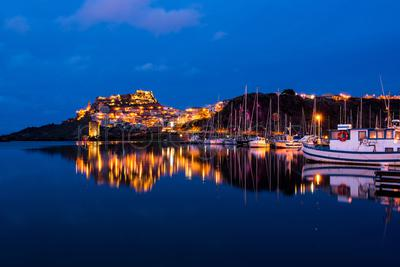 Illuminated marina and town at night