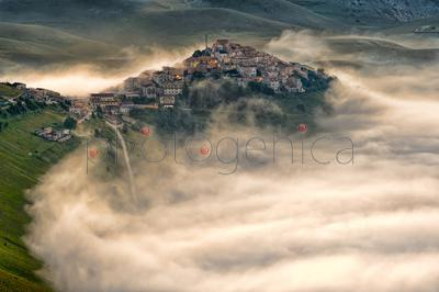 Town on hill surrounded by fog