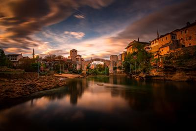 Narrow river in city flowing through arch shaped bridge under blurred sky