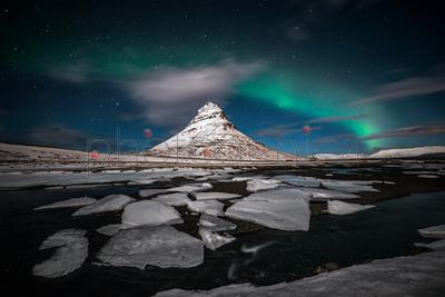 Aurora borealis and stars over mountain peak in winter