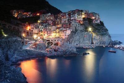 Illuminated town at coast at dusk